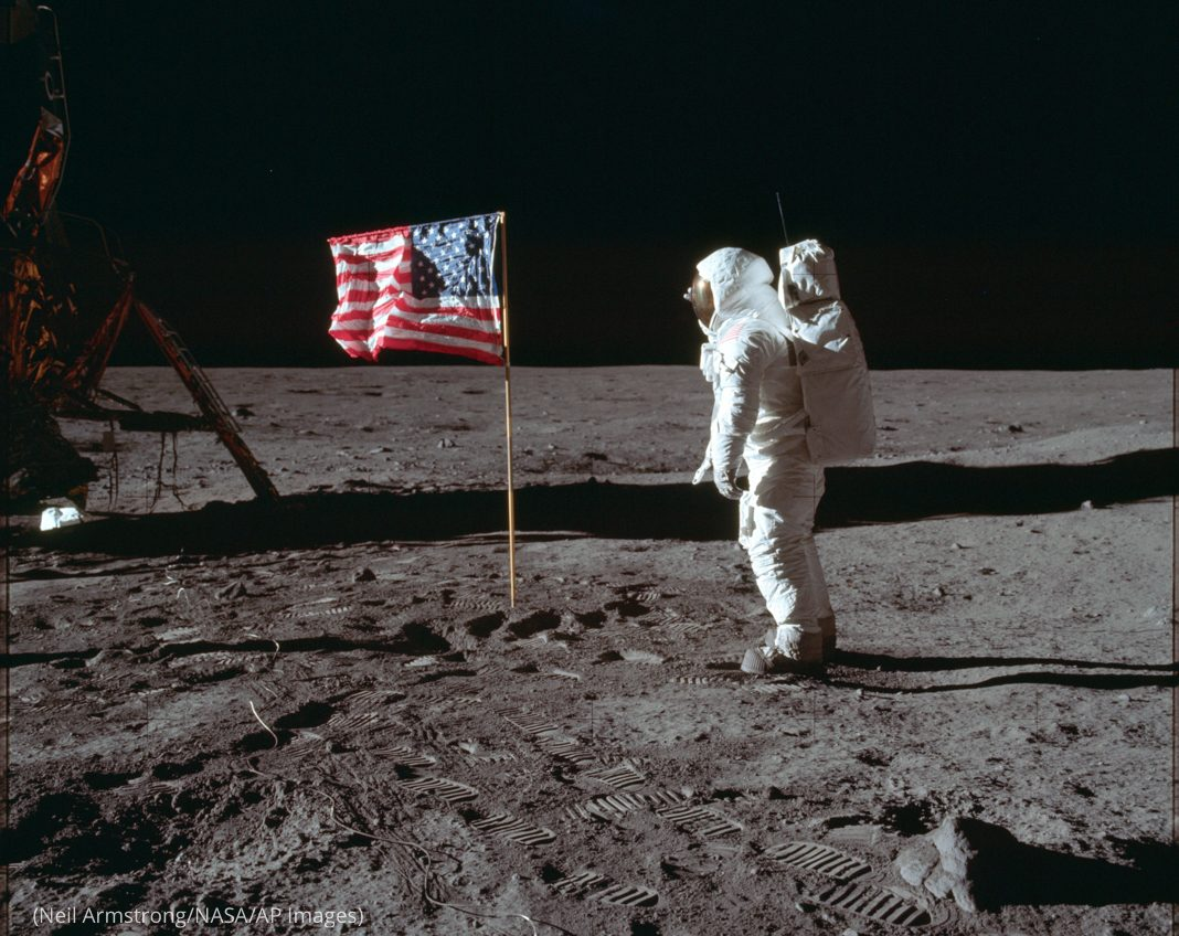 Buzz Aldrin in spacesuit next to American flag on surface of moon (Neil Armstrong/NASA/AP Images)