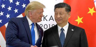 Donald Trump y Xi Jinping dándose la mano con banderas de China y Estados Unidos alrededor (© Susan Walsh/AP Images)