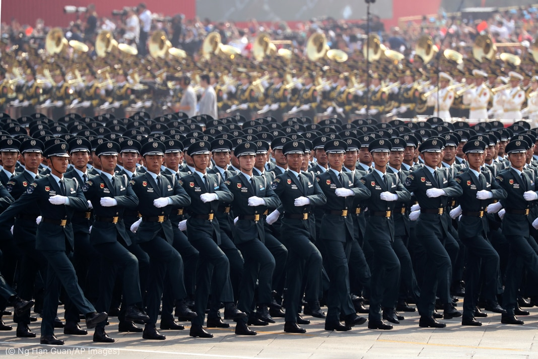 Chinese soldiers marching, with a band in the background (© Ng Han Guan/AP Images)