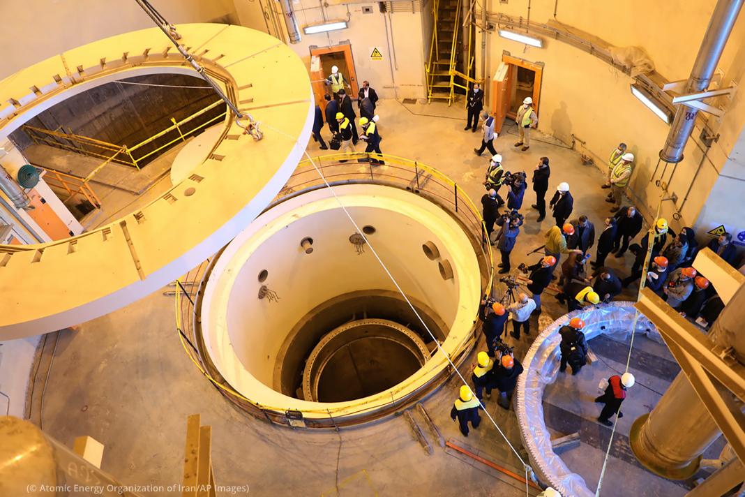 Pessoas em pé dentro de usina com grande estrutura circular no centro (© Organização de Energia Atômica do Irã/AP Images)