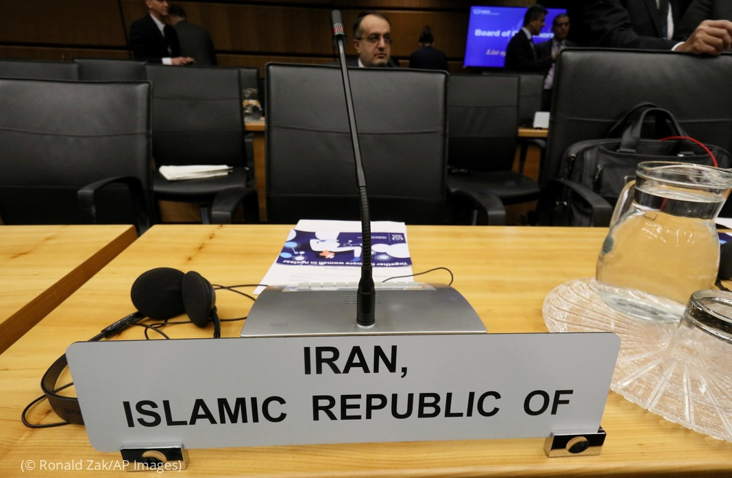 "Empty chair and microphone sitting behind sign saying ""Iran, Islamic Republic of"" (© Ronald Zak/AP Images)"