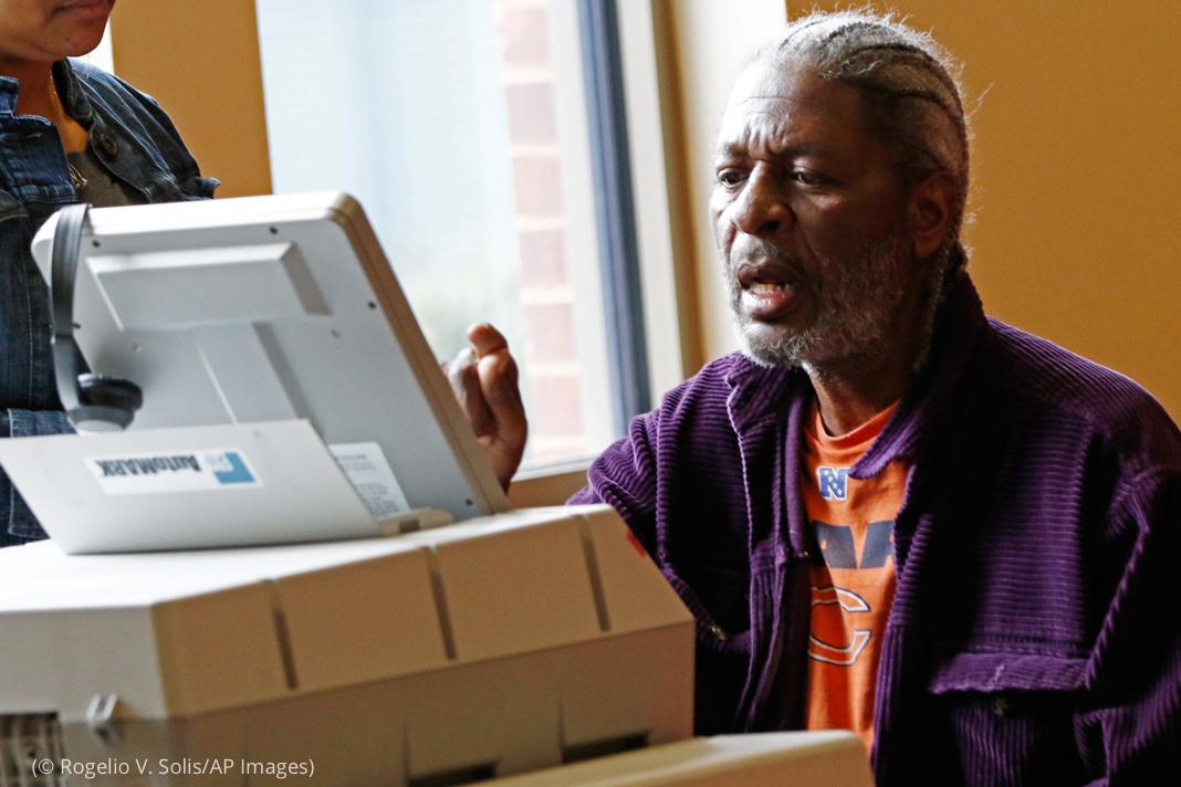 Man pressing screen on unusual machine (© Rogelio V. Solis/AP Images)