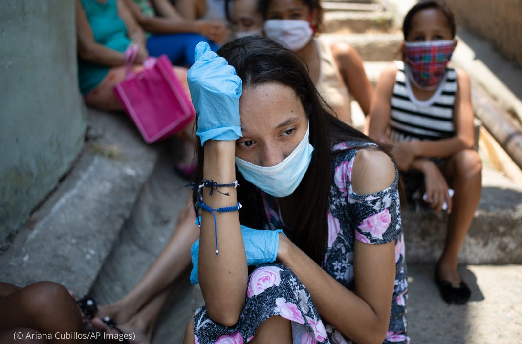 Mulher usando máscara e luvas como proteção contra o novo coronavírus sentada com outras pessoas (© Ariana Cubillos/AP Images)