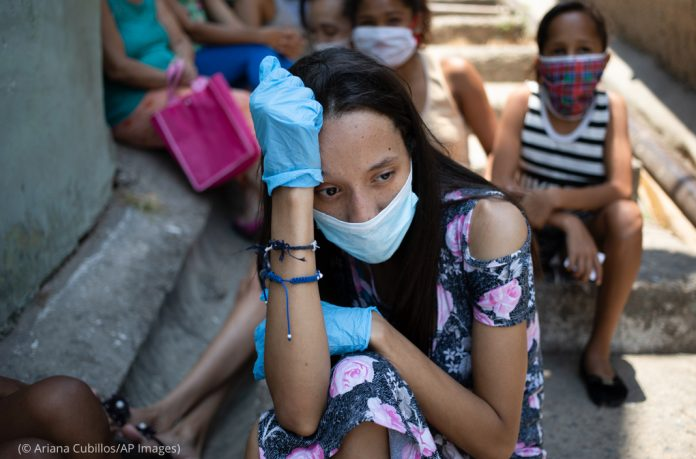 A woman wearing a mask and gloves against the spread of the new coronavirus, waits outside a soup kitchen in Venezuela (© Ariana Cubillos/AP Images)