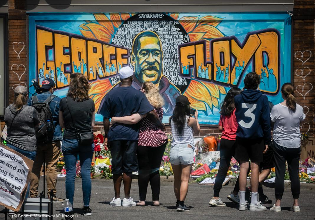 People looking at mural on wall (© Bebeto Matthews/AP Images)
