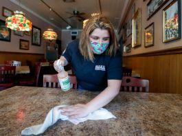 Женщина в маске и с моющим веществом в руках протирает стол (© Keith Srakocic/AP Images)