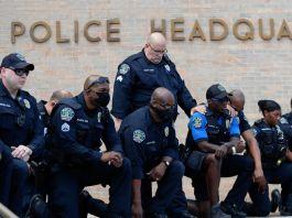 Polisi berlutut di depan markas besar polisi (© Eric Gay/AP Images)