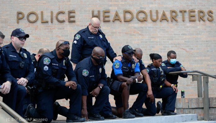 Police officers kneeling in front of police headquarters (© Eric Gay/AP Images)