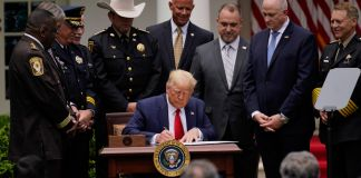 President Trump signing document surrounded by standing people (© Evan Vucci/AP Images)