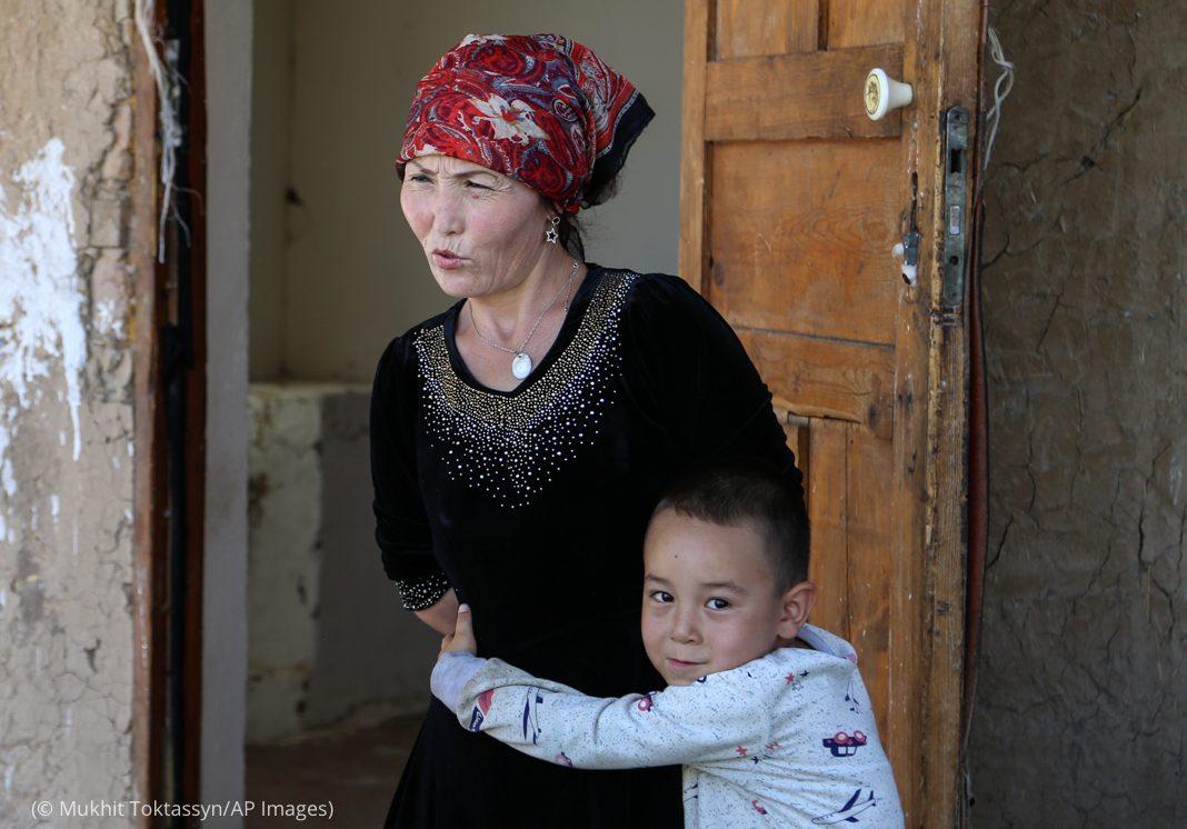 Niño pequeño abrazado a una mujer (© Mukhit Toktassyn/AP Images)