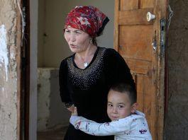 Bir kadına sarılan küçük erkek çocuk (© Mukhit Toktassyn/AP Images)
