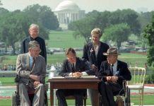 Empat orang berdiri mendampingi Presiden George H.W. Bush saat ia duduk di mejanya menandatangani dokumen (© Barry Thumma/AP Images)