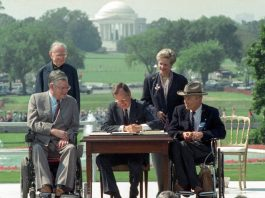 President Bush sitting at desk signing ADA into law (© Barry Thumma/AP Images)