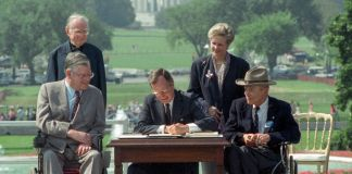 Four people around President George H.W. Bush as he sits at desk signing document (© Barry Thumma/AP Images)