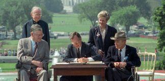 صدر جارج ایچ ڈبلیو بش ایک دستاویز پر دستخط کر رہے ہیں اور اُن کے گرد چار افراد کھڑے ہیں (© Barry Thumma/AP Images)