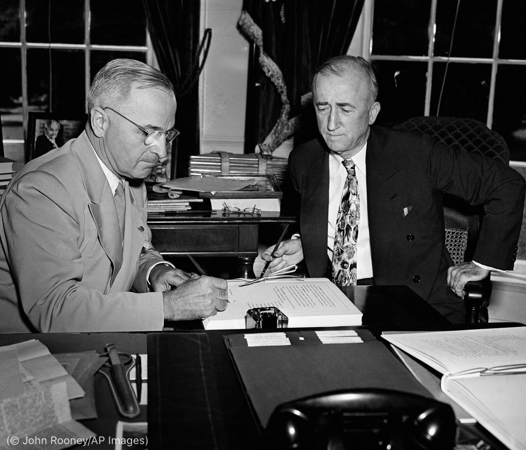 President Truman signing document as Secretary of State Byrnes sits nearby (© John Rooney/AP Images)