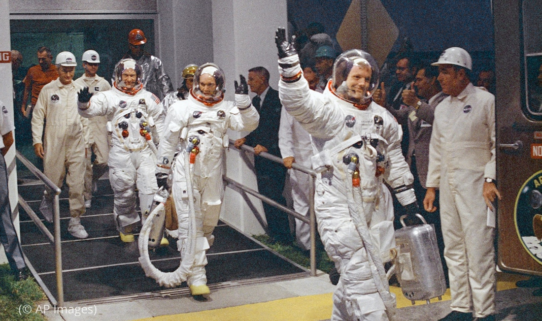 Men in spacesuits walking toward vehicle and waving to men watching them (© AP Images)