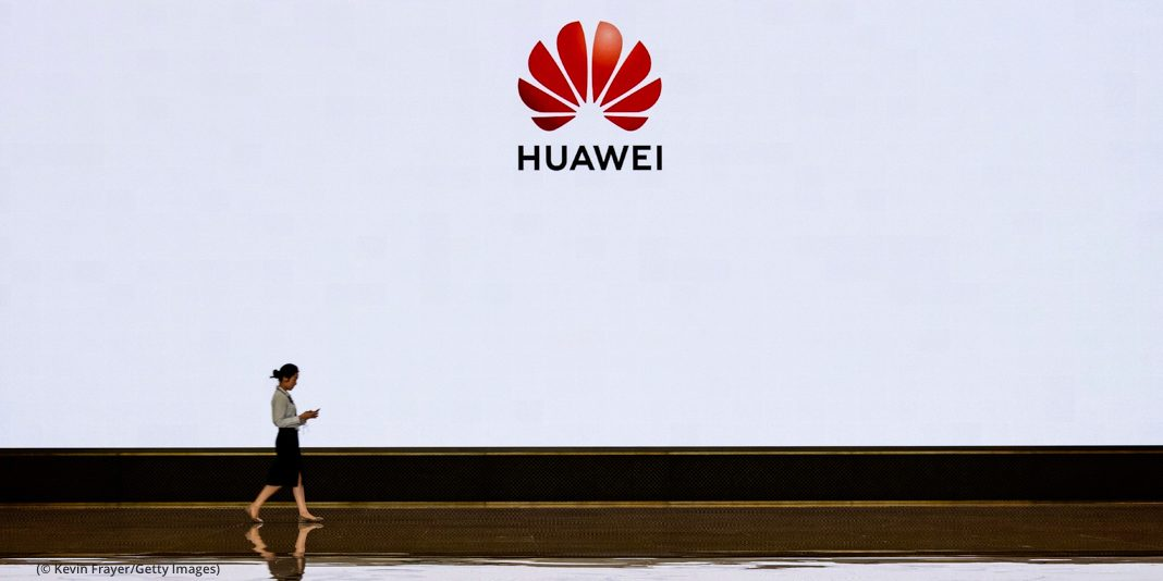 Person walking by a large white wall with a Huawei sign on it (© Kevin Frayer/Getty Images)