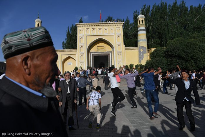 Des hommes dansant devant une mosquée (© Greg Baker/AFP/Getty Images)