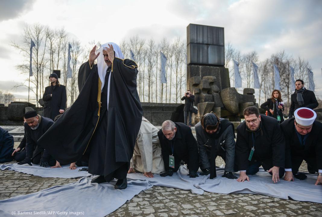 Pessoas em pé e ajoelhadas em oração (© Bartosz Siedlik/AFP/Getty Images)