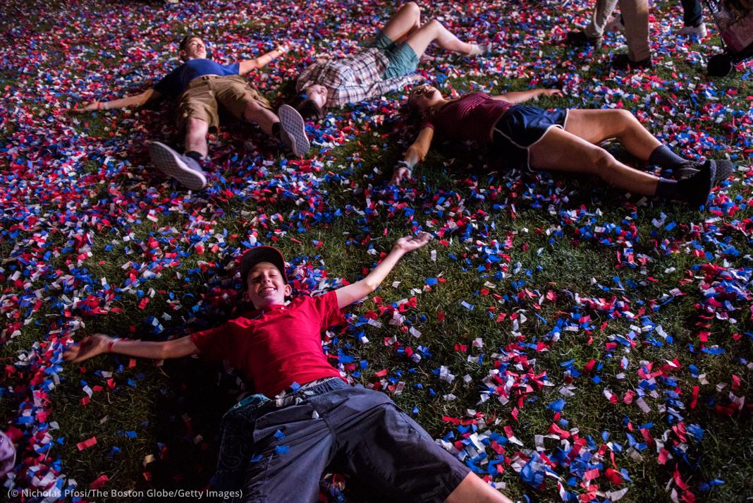 Orang-orang berbaring di rumput bertaburkan konfeti (© Nicholas Pfosi/The Boston Globe/Getty Images)