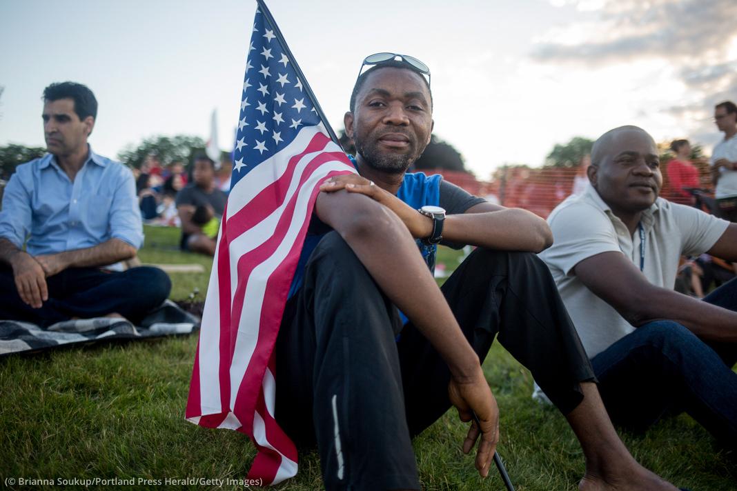 Seorang pria dengan bendera AS di pundaknya duduk diantara kerumunan di lapangan (© Brianna Soukup/Portland Press Herald/Getty Images)
