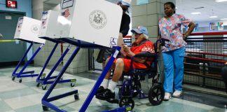 وہیل چیئر پر بیٹھی ایک خاتون ووٹنگ بوتھ استعمال کر رہی ہے (© Eduardo Munoz/Reuters)