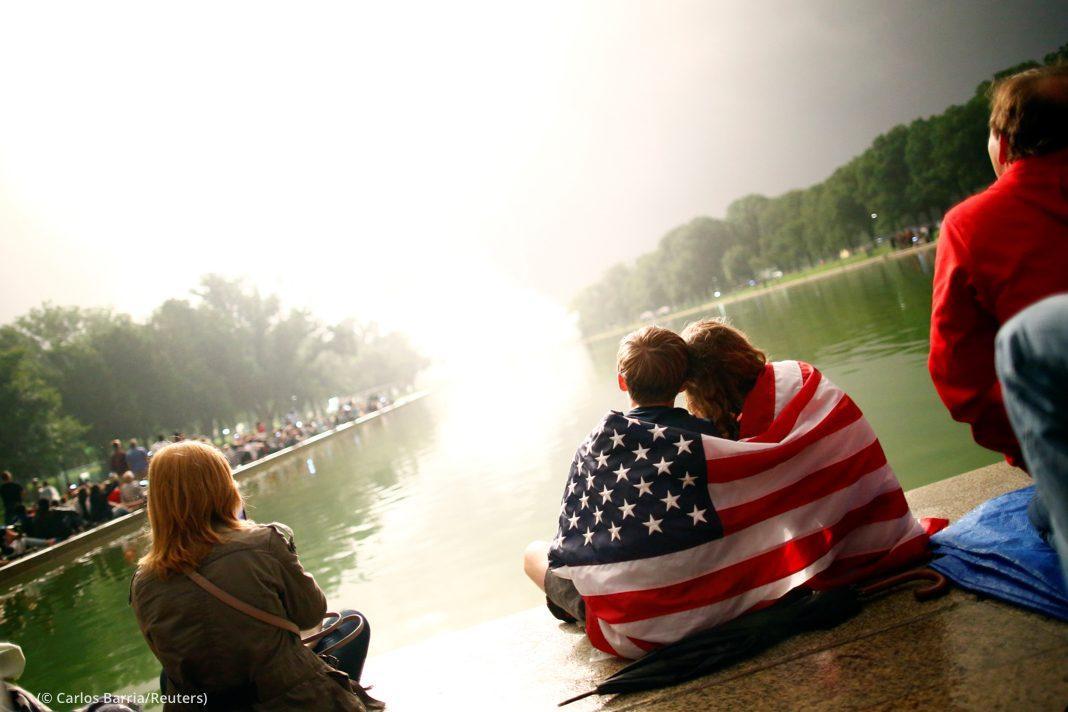 Kerumunan orang menyaksikan kembang api di samping kolam di National Mall Washington DC (© Carlos Barria/Reuters)