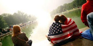 Une foule autour d'un bassin, avec deux enfants assis en premier plan, un drapeau américain leur couvrant les épaules (© Carlos Barria/Reuters)