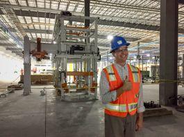 Pria berhelm berdiri di pabrik manufaktur (Courtesy of Trevor Hutchinson)
