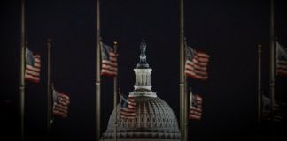 U.S. flags and dome of U.S. Capitol at night