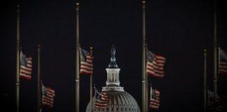 Banderas de Estados Unidos y cúpula del Capitolio de Estados Unidos en la noche
