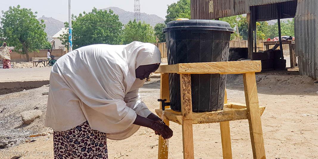 نلکے کے نیچے ہاتھ دھوتی ہوئی ایک عورت (© Mercy Corps)