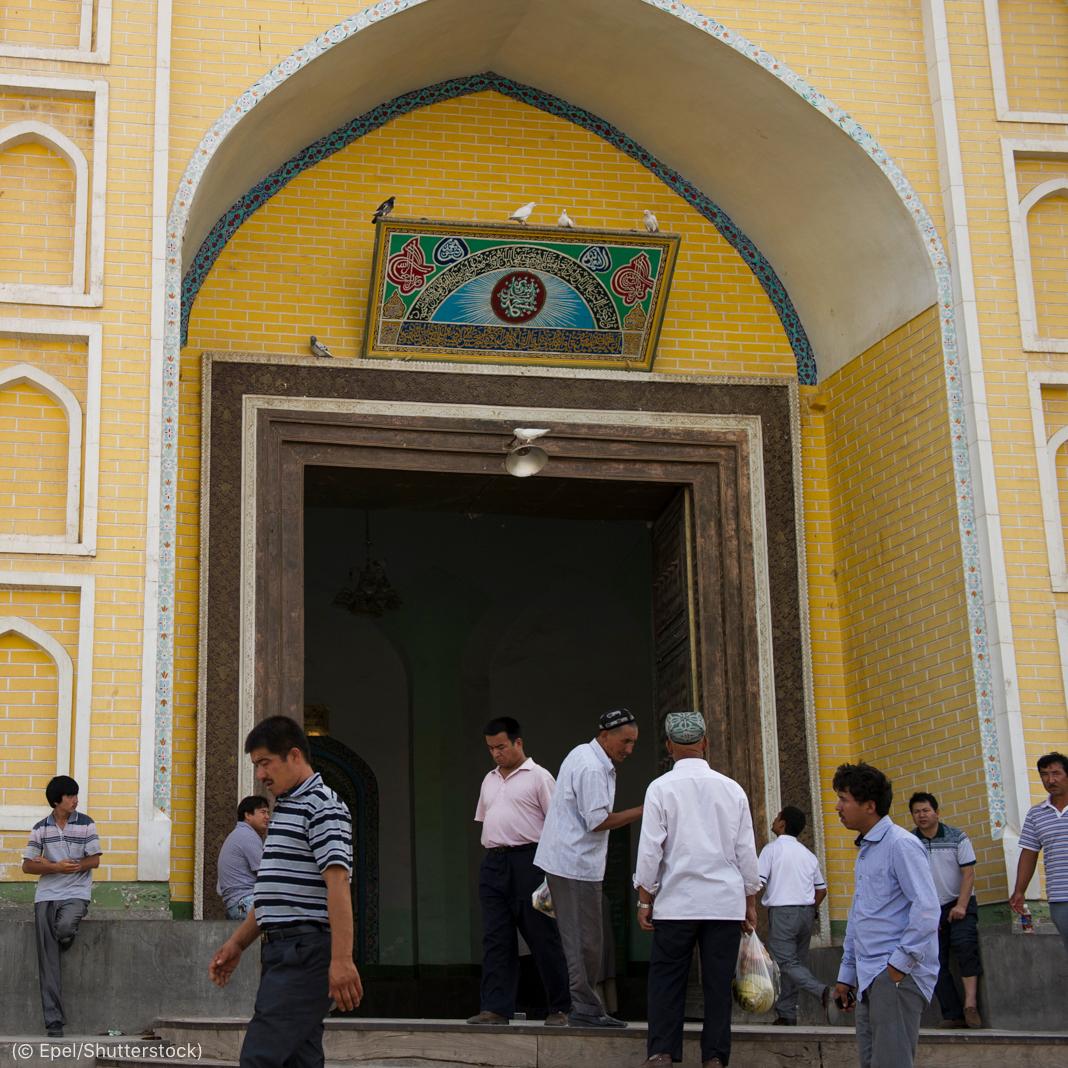 Une dizaine d'hommes devant l'entrée d'une mosquée (© Epel/Shutterstock)