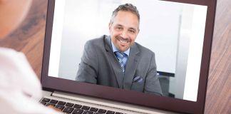 Une personne regardant un écran d'ordinateur avec l'image d'un homme souriant (© Shutterstock)