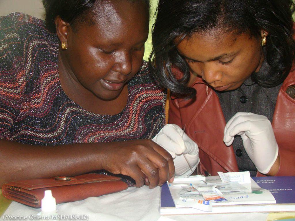 Двое женщин, одна из них в перчатках, рассматривают результаты анализа (Yvonne Otieno/MSH/USAID)