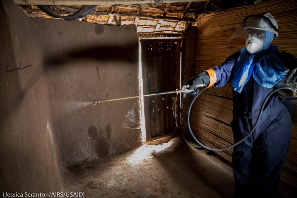 Человек в защитном костюме распыляет инсектицид в здании (Jessica Scranton/AIRS/USAID)
