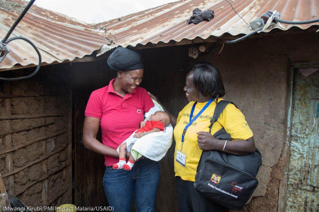Двое улыбающихся женщин, одна из них с младенцем на руках (Mwangi Kirubi/PMI Impact Malaria/USAID)