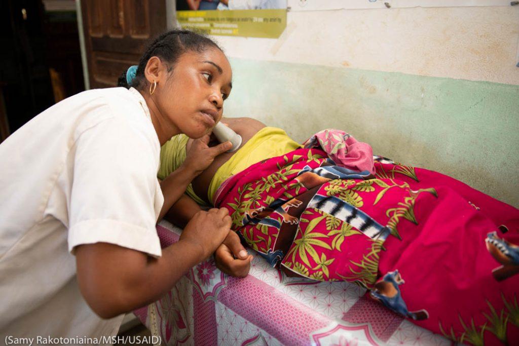Женщина проводит обследование беременной женщины (Samy Rakotoniaina/MSH/USAID)