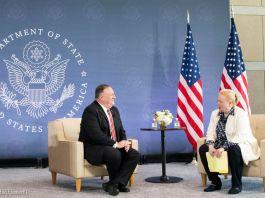 蓬佩奥国务卿和一位女士坐在美国国旗和国务院徽章旁(State Dept./Freddie Everett)