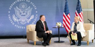 Mike Pompeo and woman sitting next to flags and the State Department seal (State Dept./Freddie Everett)