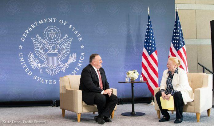 Mike Pompeo e uma mulher sentados ao lado de bandeiras e do brasão do Departamento de Estado (Depto. de Estado/Fred Everett)
