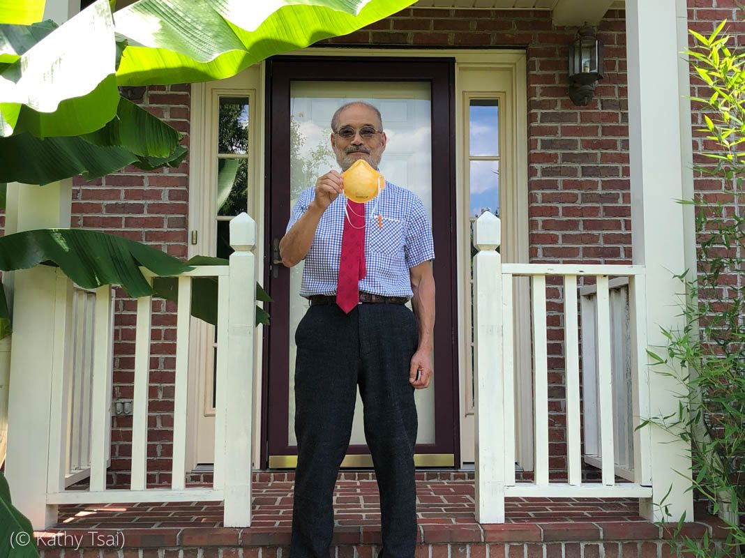 Man standing in front of house holding mask (© Kathy Tsai)