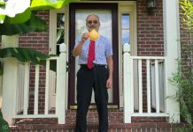 Man standing in front of a house holding an N95 mask (© Kathy Tsai)