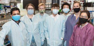 Tujuh laki-laki dan perempuan mengenakan perlengkapan pelindung berpose untuk foto di laboratorium (U.S. Army/Shawn Fury)