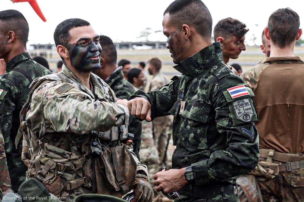 Dois soldados, um americano e outro tailandês, usando uniforme de camuflagem, se cumprimentam tocando os cotovelos em meio a grupo composto por outros soldados em campo (Cortesia: Exército Real Tailandês)