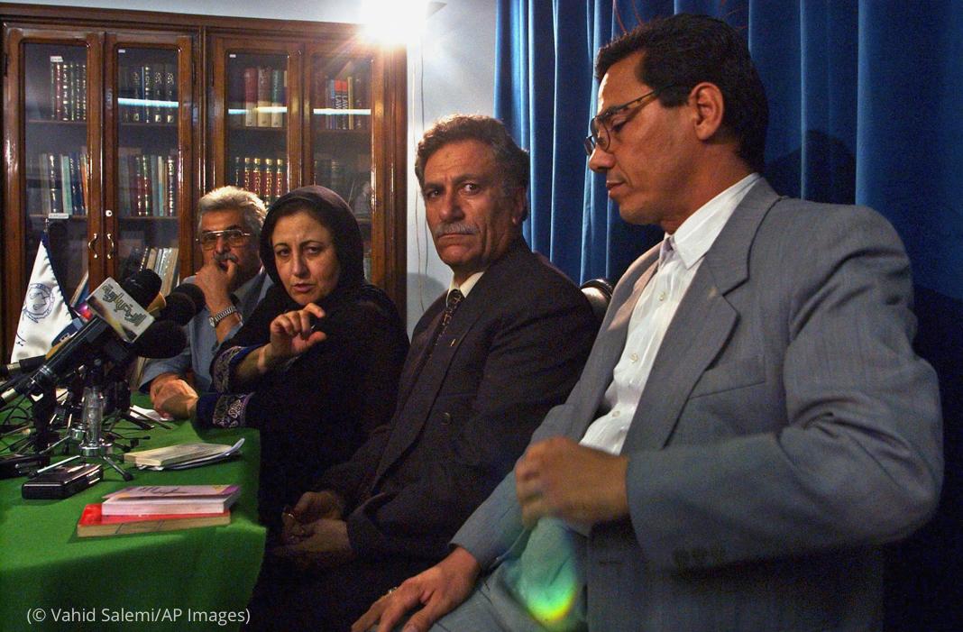 تین آدمی اور ایک عورت میز پر رکھے مائیکروفونوں کے پیچھے بیٹھے ہوئے ہیں (© Vahid Salemi/AP Images)
