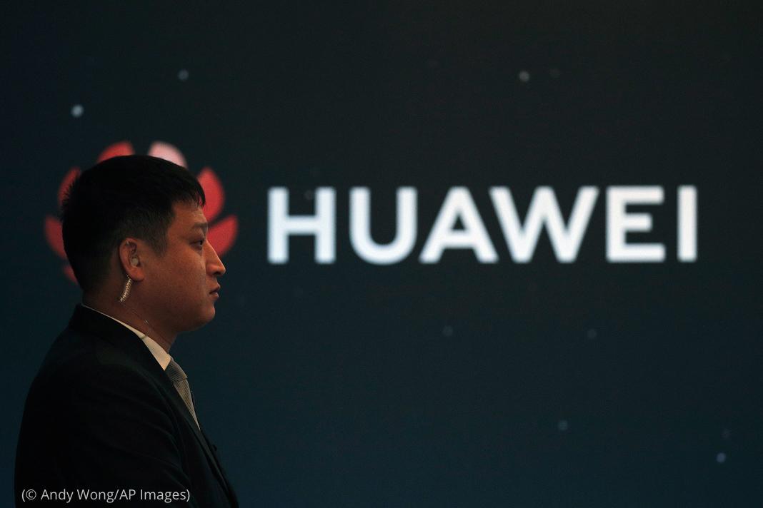 一名男子站在华为的标志前(© Andy Wong/AP Images)