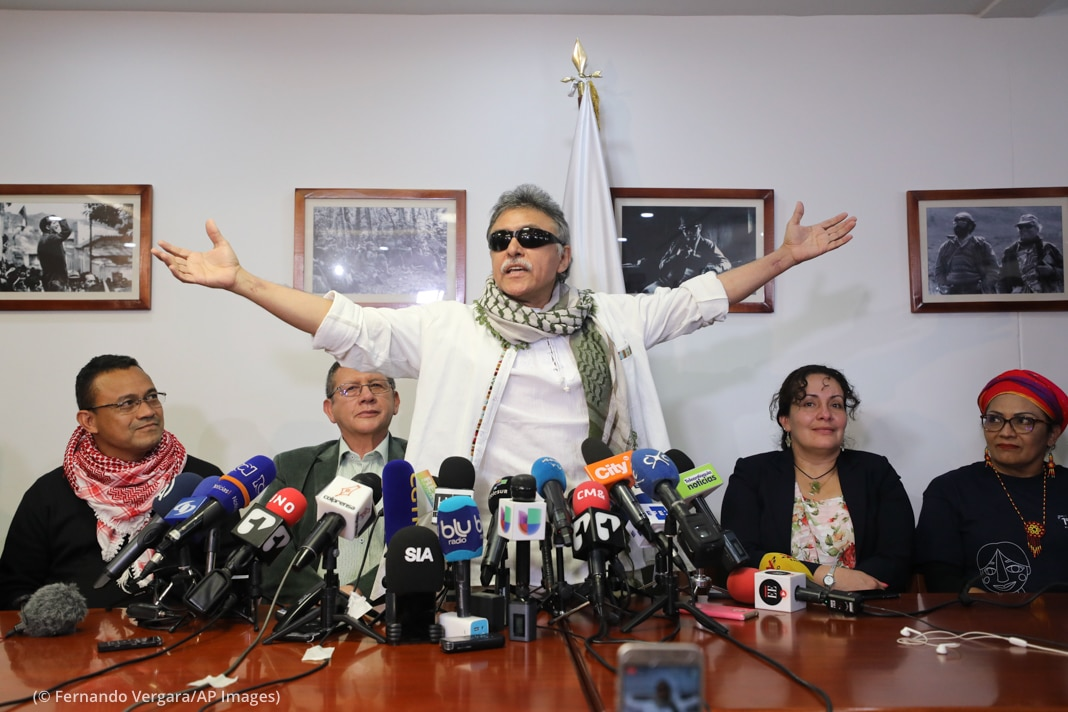 Man standing with arms raised in front of microphones with others seated behind him (© Fernando Vergara/AP Images)