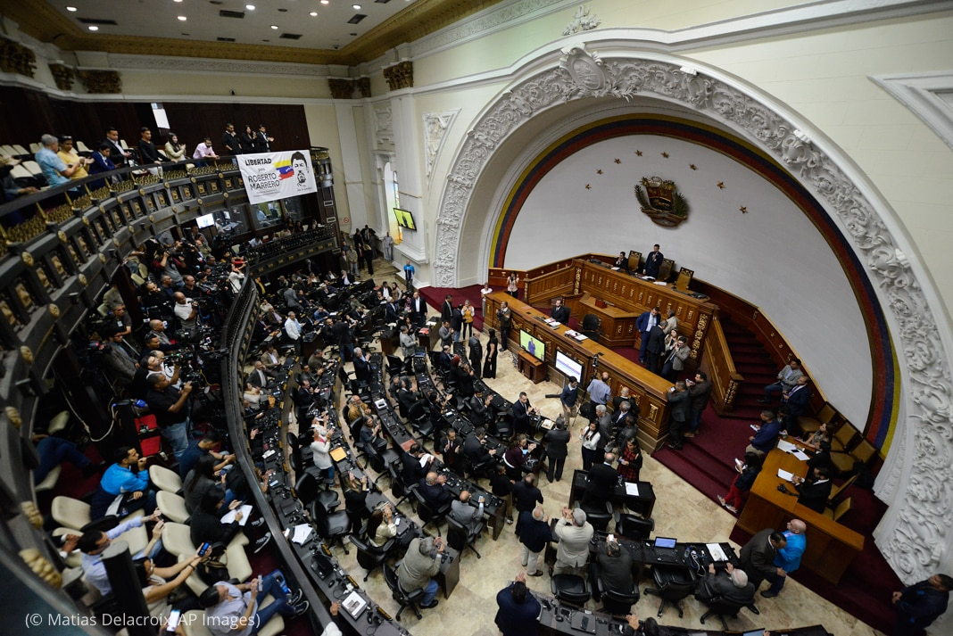 People standing and sitting inside the Venezuelan National Assembly (© Matias Delacroix/AP Images)